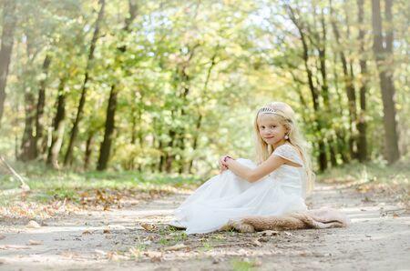 cute little girl in long white wedding dress in rural path in orange green forest