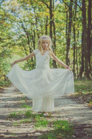 cute little girl in long white wedding dress posing in magic forest