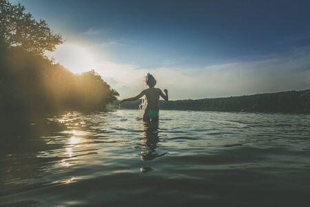 cute girl with long blond hair having fun in pond in magic golden hour time