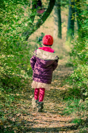 little child holding domestic cat and walking alone in sunny autumnal atmosphere Imagens - 155820836