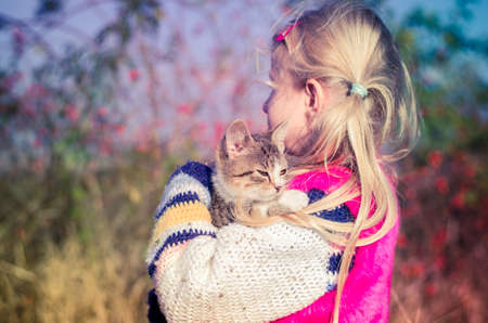 little child holding domestic cat and walking alone in sunny autumnal atmosphere Imagens - 155820759