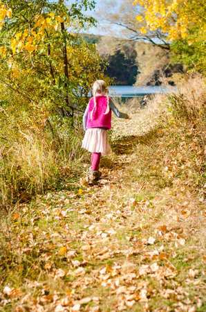 little child holding domestic cat and walking alone in sunny autumnal atmosphere