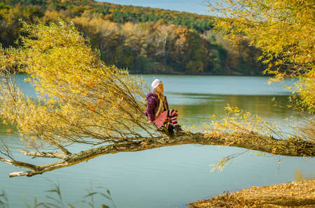 little child sitting in in the tree branch over the blue lake in scenic sunset time in colorful countryside