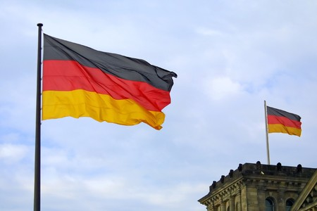National flag of Federal Republic of Germany on blue sky background photo