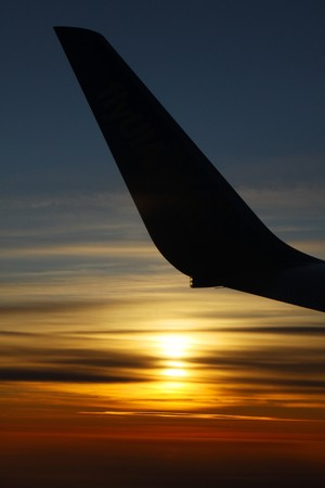 Sunrise over clouds at 30,000 feet in the air with contour of airplane wing photo