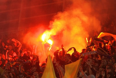 DNIPROPETROVSK, UKRAINE - OCTOBER 10, 2009: Ukrainian fans burn the fires and celebrate their victory over England after their World Cup 2010 qualifying football match at the Dnipro Arena on October 10, 2009 in Dnipropetrovsk, Ukraine. Ukraine won 1:0