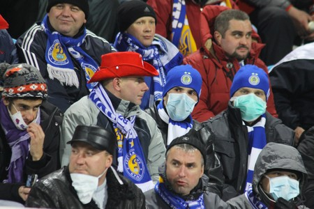 ah1n1: KIEV, UKRAINE - NOVEMBER 4, 2009: Dynamo Kiev fans weared protective masks and filled up the stadium during an UEFA CL match despite fears of the spread of the AH1N1 virus on Nov 4, 2009 in Kiev Editorial