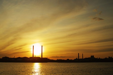 Sun settings behind power plant pipes photo