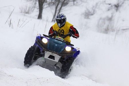 KYIV, UKRAINE - 13 FEBRUARY 2010: The quad bike's driver Vyacheslav Dovbysh (Yamaha Grizzly 700) rides over snow track during Baja Kyiv-2010 Rally on 13 Feb, 2010 in Kyiv Stock Photo - 7863743