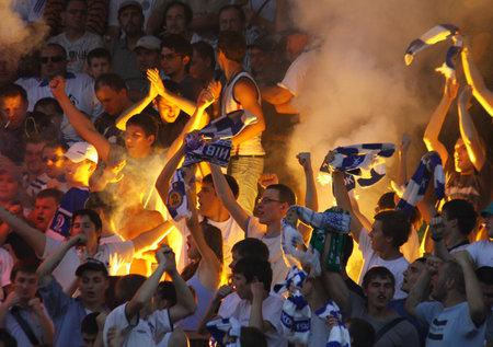 ultras: KYIV, UKRAINE - JULY 9, 2010: Dynamo Kyiv ultras (ultra supporters) burn a flares during first game of Ukraine Championship season 201011 against FC Obolon on July 9, 2010 in Kyiv, Ukraine