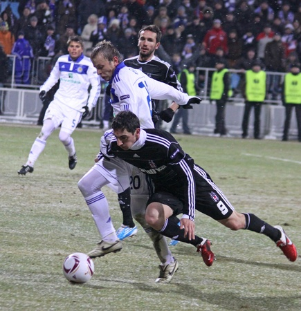 KYIV, UKRAINE - FEBRUARY 24, 2011: Oleg Gusev of Dynamo Kyiv (#20, in white) fights for a ball with Roberto Hilbert of Besiktas (#9) during their UEFA Europa League game on February 24, 2011 in Kyiv, Ukraine Stock Photo - 9020933