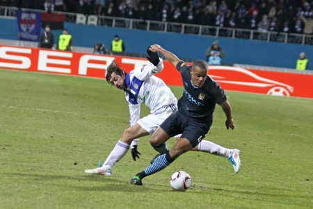uefa: KYIV, UKRAINE - MARCH 10, 2011: Artem Milevskiy of Dynamo Kyiv (L) fights for a ball with Vincent Kompany of Manchester City during their UEFA Europa League game on March 10, 2011 in Kyiv, Ukraine