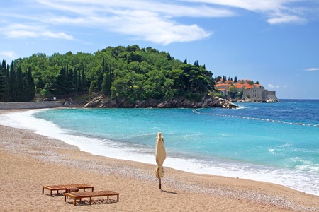 Empty beach with two chairs and umbrella near Sveti Stafan island, Montenegro Stock Photo - 9216213