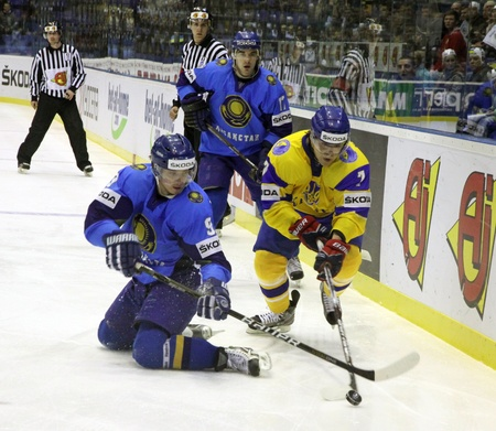 icehockey: KYIV, UKRAINE - APRIL 23, 2011: Konstantin Pushkaryov of Kazakhstan (L) fights for a puck with Oleg Shafarenko of Ukraine during their IIHF Ice-hockey World Championship DIV I Group B game on April 23, 2011 in Kyiv, Ukraine