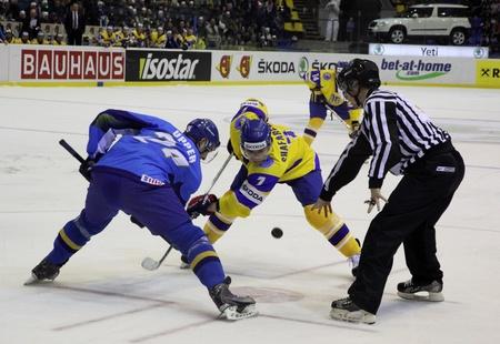 div: KYIV, UKRAINE - APRIL 23, 2011: Dmitri Upper of Kazakhstan (L) fights for a puck with Oleg Shafarenko of Ukraine during their IIHF Ice-hockey World Championship DIV I Group B game on April 23, 2011 in Kyiv, Ukraine