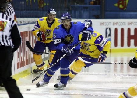 div: KYIV, UKRAINE - APRIL 23, 2011: Talgat Zhailauov of Kazakhstan (in Blue) fights for a puck with Ukrainian players during their IIHF Ice-hockey World Championship DIV I Group B game on April 23, 2011 in Kyiv, Ukraine Editorial