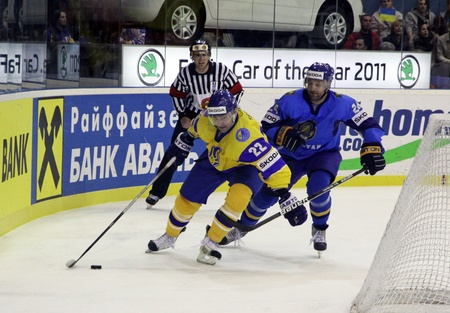 div: KYIV, UKRAINE - APRIL 23, 2011: Dmytro Tsyrul of Ukraine (L) fights for a puck with Dmitri Upper of Kazakhstan during their IIHF Ice-hockey World Championship DIV I game on April 23, 2011 in Kyiv