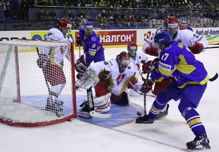 KYIV, UKRAINE - April 18, 2011: Olexander Materukhin of Ukraine (R in Blue) fights for a puck with Lithuanian players during their IIHF Ice-hockey World Championship DIV I Group B game on April 18, 2011 in Kyiv, Ukraine
