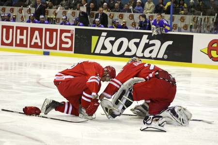 div: KYIV, UKRAINE - APRIL 20, 2011: Marcin Kolusz of Poland (L) helps goalkeeper to lace his shoes during IIHF Ice-hockey World Championship DIV I Group B game against Ukraine on April 20, 2011 in Kyiv, Ukraine Editorial