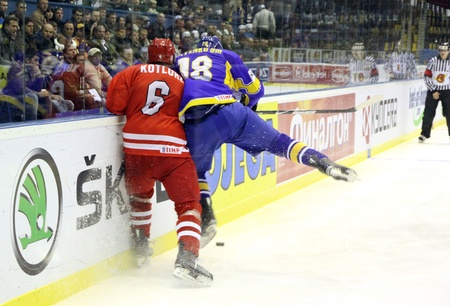 KYIV, UKRAINE - APRIL 20, 2011: Michal Kotlorz of Poland (L) fights for a puck with Dmytro Isayenko of Ukraine during their IIHF Ice-hockey World Championship DIV I Group B game on April 20, 2011 in Kyiv, Ukraine Stock Photo - 9475166
