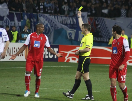 booked: KYIV, UKRAINE - APRIL 7, 2011: Referee Bjorn Kuipers shows the yellow card to Paulo Cesar of SC Braga (R) during UEFA Europa League game against FC Dynamo Kyiv on April 7, 2011 in Kyiv, Ukraine