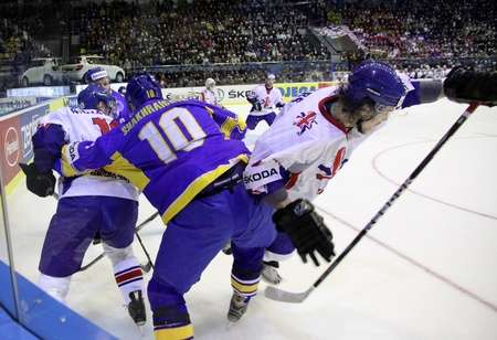 icehockey: KYIV, UKRAINE - April 17, 2011: Vadym Shakhraichuk of Ukraine fights for a puck with Matthew Myers of Great Britain during their IIHF Ice-hockey World Championship DIV I Group B game on April 17, 2011 in Kyiv, Ukraine