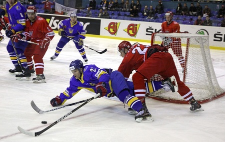 icehockey: KYIV, UKRAINE - APRIL 20, 2011: Artem Gnidenko of Ukraine (L) fights for a puck with Tomasz Kozlowski of Poland during their IIHF Ice-hockey World Championship DIV I Group B game on April 20, 2011 in Kyiv, Ukraine