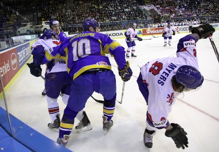 div: KYIV, UKRAINE - April 17, 2011: Vadym Shakhraichuk of Ukraine fights for a puck with Matthew Myers of Great Britain during their IIHF Ice-hockey World Championship DIV I Group B game on April 17, 2011 in Kyiv, Ukraine