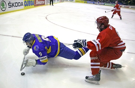 div: KYIV, UKRAINE - APRIL 20, 2011: Dmytro Nimenko of Ukraine (L) fights for a puck with Michal Kotlorz of Poland during their IIHF Ice-hockey World Championship DIV I Group B game on April 20, 2011 in Kyiv, Ukraine
