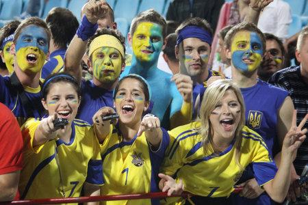 react: KYIV, UKRAINE - JUNE 1, 2011: Ukrainian soccer fans react after Ukraine beat of Uzbekistan in their Frienfly game on June 1, 2011 in Kyiv, Ukraine