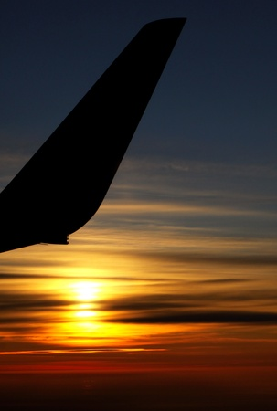 Sunrise over clouds with contour of airplane wing photo