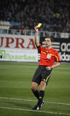 booked: KYIV, UKRAINE - OCTOBER 20, 2011: Referee Milorad Mazic shows the yellow card during UEFA Europa League game between Dynamo and Besiktas on October 20, 2011 in Kyiv, Ukraine