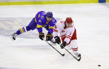 kyiv: KYIV, UKRAINE - NOVEMBER 11, 2012: Artem Bondaryev of Ukraine (in Blue) fights for a puck with Tomasz Malasinski of Poland during their ice-hockey pre-olympic qualification game on November 11, 2012 in Kyiv, Ukraine