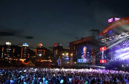 KYIV, UKRAINE - JUNE 30, 2012: People look on Sir Elton John performs onstage during charity Anti-AIDS concert at the Independence Square on June 30, 2012 in Kyiv, Ukraine