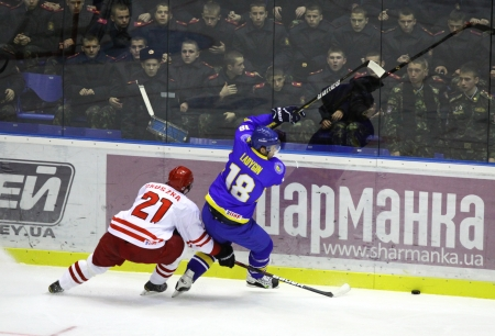 icehockey: KYIV, UKRAINE - NOVEMBER 11, 2012: Mykola Ladygin of Ukraine (in Blue) fights for a puck with Dariusz Gruszka of Poland during their ice-hockey pre-olympic qualification game on November 11, 2012 in Kyiv, Ukraine