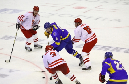 icehockey: KYIV, UKRAINE - NOVEMBER 11, 2012: Ukraine (in Blue) and Poland ice-hockey players fight for a puck during their pre-olympic qualification game on November 11, 2012 in Kyiv, Ukraine