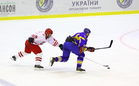 icehockey: KYIV, UKRAINE - NOVEMBER 11, 2012: Mykola Ladygin of Ukraine (in Blue) fights for a puck with Marek Strzyzowski of Poland during their ice-hockey pre-olympic qualification game on November 11, 2012 in Kyiv, Ukraine