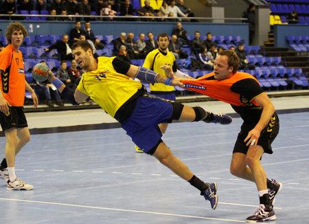 KIEW, UKRAINE - 2. April 2013: Dmytro Doroshchuk der Ukraine (in gelb) angreifen Netz während Handball EHF EURO 2014 Qualifikationsspiel gegen die Niederlande am 2. April 2013 in Kiew, Ukraine