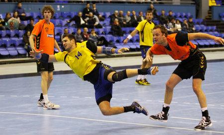KIEV, UKRAINE - 2 avril 2013: Dmytro Doroshchuk de l'Ukraine (en jaune) attaquent le net au cours de handball EHF EURO 2014 match de qualification contre Pays-Bas, le 2 Avril 2013, à Kiev, Ukraine Éditoriale