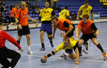 terrain de handball: KIEV, UKRAINE - 2 avril 2013: Pays-Bas joueurs de handball (en orange) d�fendre leur EHF EURO net au cours de match de qualification 2014 contre l'Ukraine le 2 Avril 2013, � Kiev, Ukraine