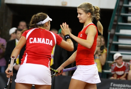 KYIV, UKRAINE - APRIL 21, 2013: Eugenie Bouchard (R) and Sharon Fichman of Canada cheer up each other during BNP Paribas FedCup game against Lesia Tsurenko and Elina Svitolina of Ukraine on April 21, 2013 in Kyiv, Ukraine