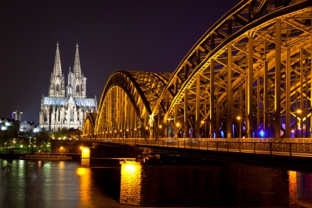 Riverside night view of Cologne Cathedral and railway bridge over the Rhine river, Germany photo