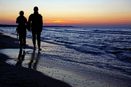 unrecognizable people: Couple of unrecognizable people enjoying a beach walk at sunset