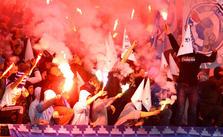 KYIV, UKRAINE - APRIL 16, 2014  FC Dynamo Kyiv ultras  ultra supporters  burn flares during Ukraine Championship game against Shakhtar Donetsk at NSC Olimpiyskiy stadium in Kyiv