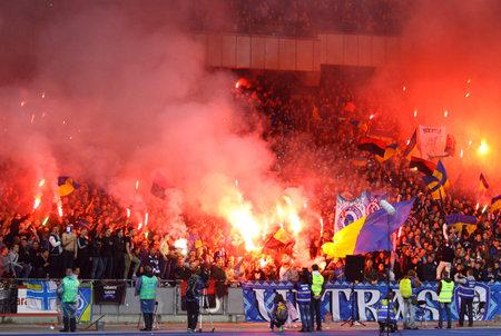 ultras: KYIV, UKRAINE - APRIL 16, 2014  FC Dynamo Kyiv ultras  ultra supporters  burn flares during Ukraine Championship game against Shakhtar Donetsk at NSC Olimpiyskiy stadium in Kyiv Editorial