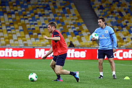 midfielder: KYIV, UKRAINE - SEPTEMBER 9, 2013  James Milner  L  and coach Gary Neville of England run during training session at NSC Olympic stadium before FIFA World Cup 2014 qualifier game against Ukraine