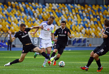 KYIV, UKRAINE - MAY 18, 2014  Andriy Yarmolenko of Dynamo Kyiv  in White  fights for a ball with FC Zorya Luhansk players during their Ukraine Championship game at Olympic stadium in Kyiv