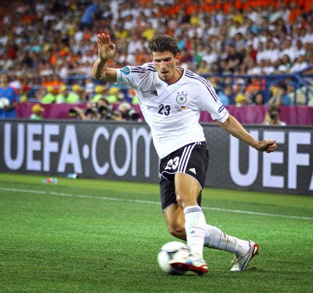 2012 년 6 월 13 일 KHARKIV, 우크라이나 - 독일의 마리오 고메즈는 네덜란드와 UEFA 유로 2012 경기 중 공을 조종한다. 에디토리얼