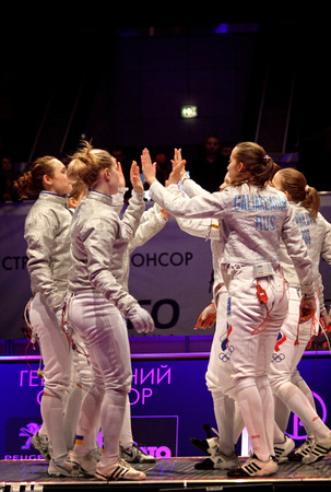 fencers: KYIV, UKRAINE - APRIL 13, 2012  Ukrainian and Russian fencers cheer each other up before Womens Sabre final match of World Fencing Championships Editorial