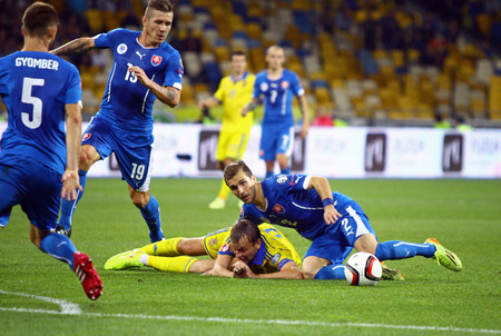 gusev: KYIV, UKRAINE - SEPTEMBER 8, 2014: Oleh Gusev of Ukraine (in Yellow) fights for a ball with Slovakian players during their UEFA EURO 2016 Qualifying game
